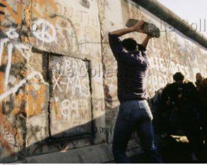 Allemagne. La Chute du Mur de Berlin. Homme jetant une pierre contre le Mur. 1989. Photographie. Collection particulière.