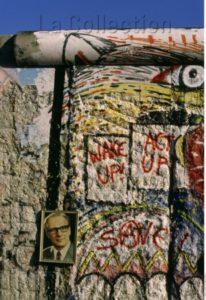 Allemagne. La Chute du Mur de Berlin. Reste du Mur auquel est accroché un portrait d'Erich Honecker. Vers 1989 1990. Photographie. Collection particulière.
