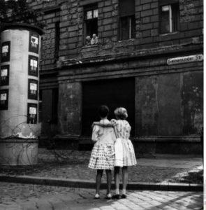 Allemagne. Guerre froide. Berlin Wedding. Petites filles et couple de personnes âgées discutant par de là le dispositif de barbelés dans la zone frontière. 1961. Photographie. Collection particulière.