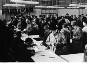 Allemagne. Guerre froide. Berlin, Tempelhof. Bureau des laissez passer dans le hall de la Friedrich Ebert Sportplatz. 1964. Photographie. Collection particulière.