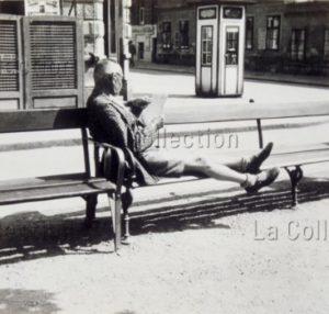 Homme lisant assis sur un banc public. Vers 1930. Photographie. Collection particulière.