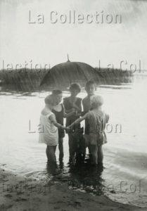 Anonyme. Enfants au bord d'un lac sous la pluie. Allemagne, vers 1925. Photographie. Collection particulière.