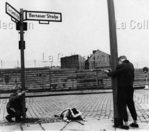 """Allemagne. Guerre Froide. Berlin, Wedding. Enfants de Berlin-Ouest jouant aux """"vopos"""" et aux fugitifs à l'angle de la Bernauer Strasse et de la Gärdenstrasse. 1965. Photographie. Collection particulière."""
