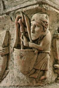 France. St-Parize-le-Châtel. Chapiteau. Cuisinier diabolique tournant sa cuillière dans une marmite. XIIe siècle. Sculpture.