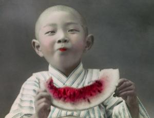 Teijiro Tagaki. Jeune Japonais mangeant une tranche de pastèque. Vers 1900-1915. Photographie. Collection particulière.