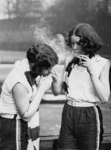 Anonyme. Deux membres du Club d'Aviron pour femme du service civil, fumant une cigarette près de la Tamise. Vers 1930. Photographie. Collection particulière.
