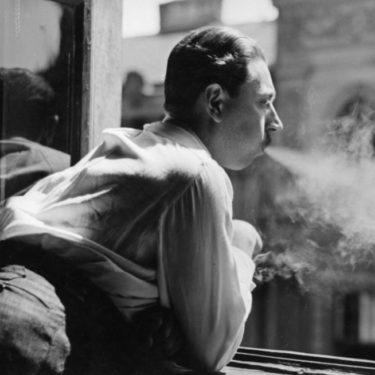 Anonyme. Un fumeur accoudé à la fenêtre. Vers 1935. Photographie. Collection particulière.